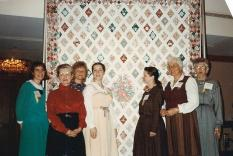 Quilters showing off the quilt, 1988 AGM
